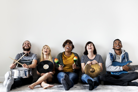 A group of young people are sat against a white wall, each holding a different instrument looking towards the sky smiling
