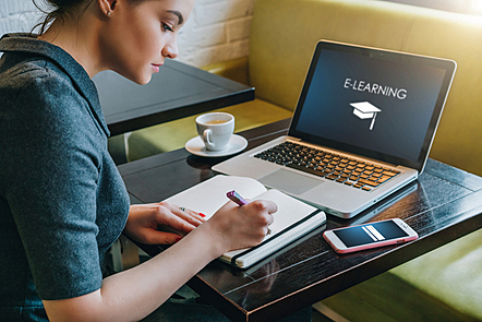 A young businesswoman sitting in a café revising on her online course.