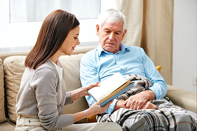 Care worker reads to elderly man sat on settee