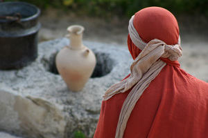Robed person looking down at water well
