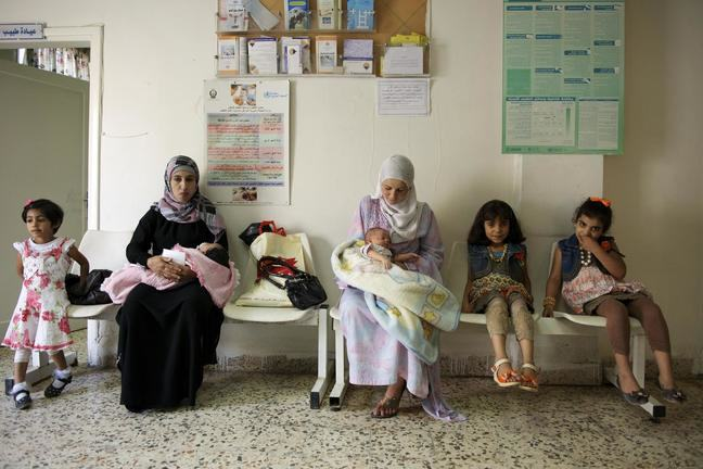 Two mothers holding their babies are shown sitting in a waiting room. Other small children sit on chairs nearby.