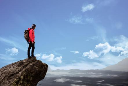 Person with a rucksack at the top on a large rock overlooking a valley from a high height