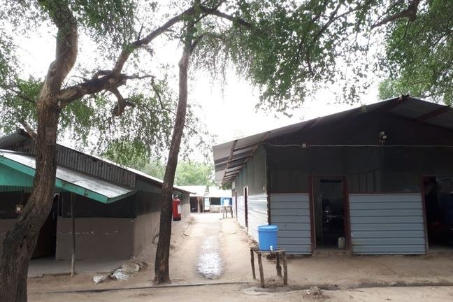 A hospital buildings in South Sudan. The buildings are basic with corrugated roofs. Outside is a makeshift water tank with tap dispenser for hand washing.