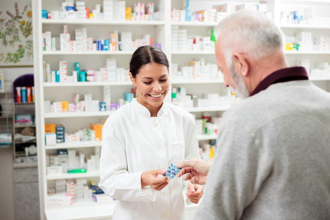 A smiling pharmacist handing over medication to an elderly gentleman whilst behind a counter with a backdrop of shelves containing medicines