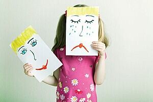The image is of a young girl holding up a photo of a happy and another of a sad face.