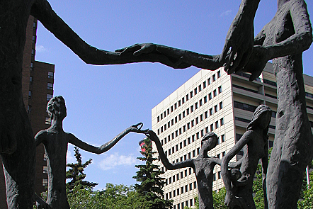'Family of Man' sculpture (in Calgary) with figures holding hands ; statues first built by Mario Hubert Armengol for Britain's Pavilion at Expo 67 in Montreal