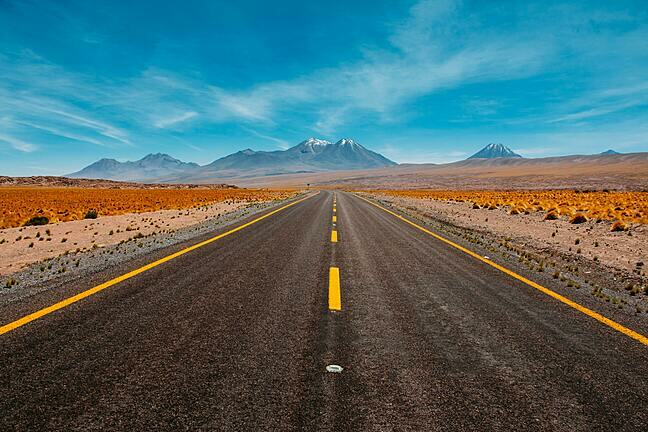 Road stretching out in to the distance with mountains on the horizon on a bright, sunny day.