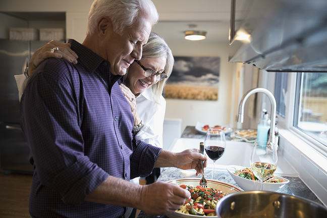 Senior couple cooking and drinking wine in kitchen