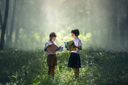 Two children reading in the middle of a brightly lit wood.