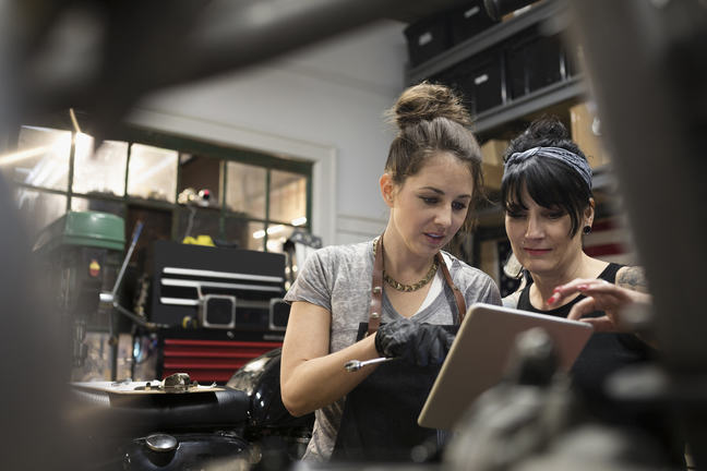 Two women working in a mechanics looking at an iPad to assist them with their work.