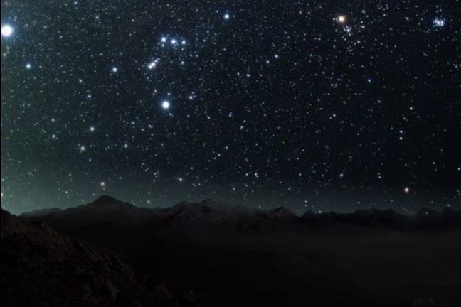 The image is of the night sky with hundreds of stars visible, the bottom half of the Orion constellation is just in view. In the foreground of the image you can see a rocky terrain.