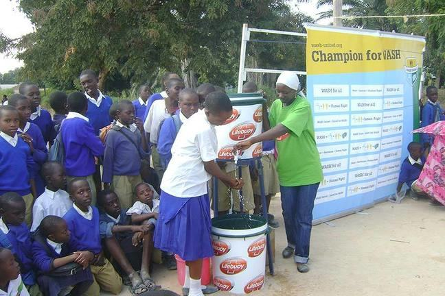 Group of schoolchildren watch a hand washing demonstration