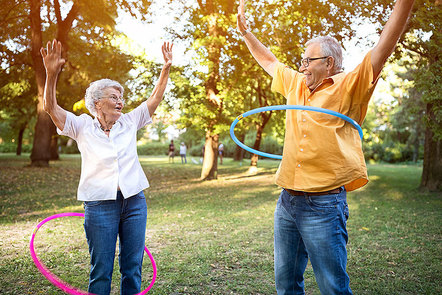 Older couple in a park using hoola hoops