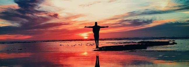 Person embracing an amazing sunset, as if looking into the future