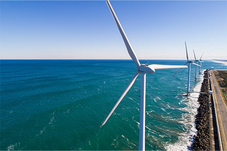 A line of four wind turbines by the sea.