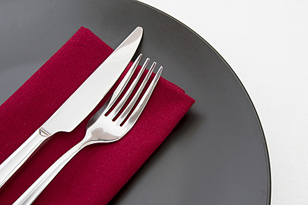 Cutlery on red napkin with black plate.