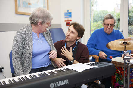 A male music therapist talks to an elderly lady sat in front of an electric keyboard