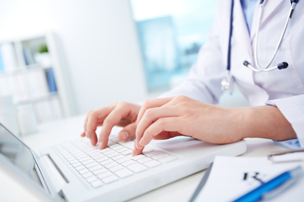 Healthcare professional using computer.