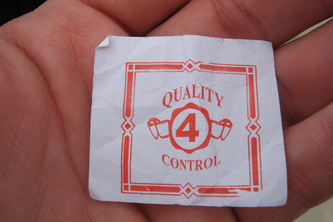 Quality control typed on a piece of paper in the palm of a hand
