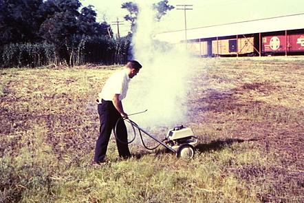 A man in a white shirt and black trousers in a field operates a machine which looks like a lawnmower, which disperses an airborne insecticide in a white cloud of vapour.