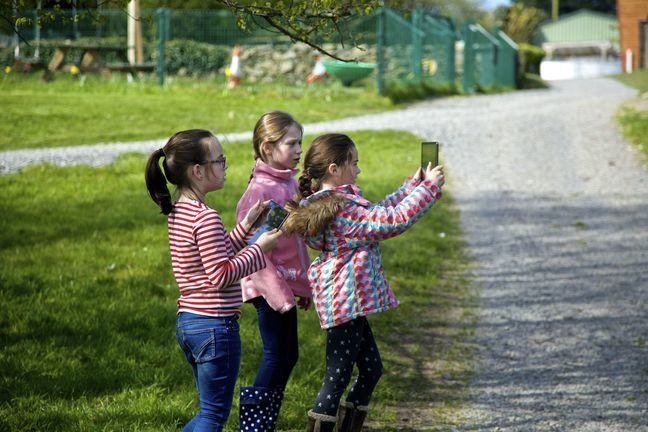 Scene of children filming in the park with a tablet