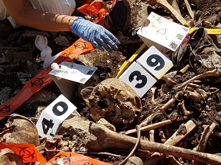A pile of disarticulated human remains at the base of a cliff. Some numbers and some tape have been placed nearby to record the remains