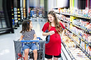 A pregnant woman in a supermarket aisle. Her young daughter is next to her sat in a supermarket trolley