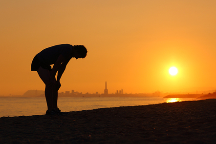 Silhouette of an tired sportsman at sunset.