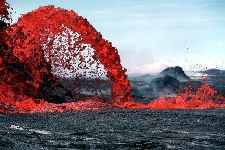 Arching fountain of red lava exploding out of the ground and being scattered.