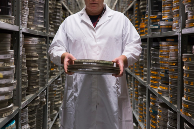 A man in a white coat retrieving reels of film from the warehouse at the BFI National Archive