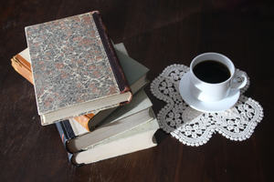 Books set down on table with tea cup