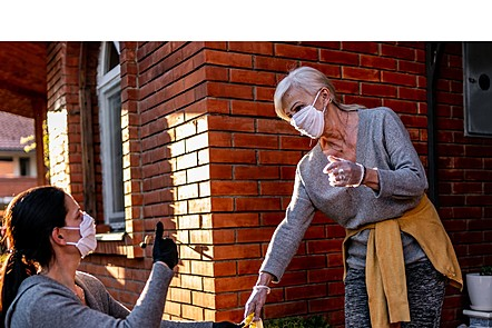 two women in face masks and gloves, one is handing the other shopping
