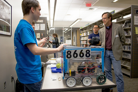 Two people explaining a robot buggy to two other people in a library