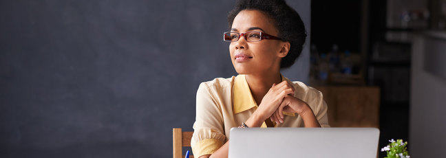 Woman sitting at work desk contemplating