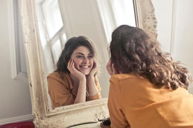 Vrouw die in de spiegel kijkt