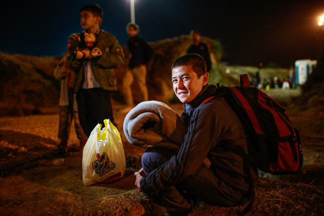 An unaccompanied teenager is crouching on the ground holding a blanket and carrying a backpack. It is night time and he is smiling at the camera. There are other unaccompanied children and adult refugees standing nearby.