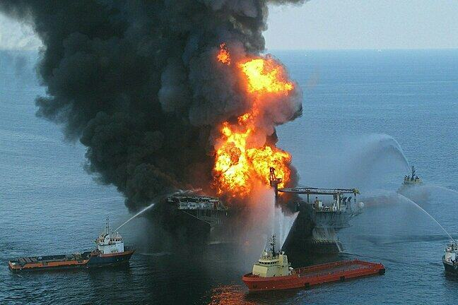 This image shows an oil rig in the middle of the ocean in flames.