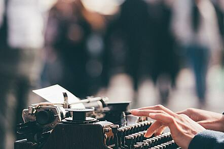 A pair of hands typing on an old-fashioned typewriter, viewed in profile.