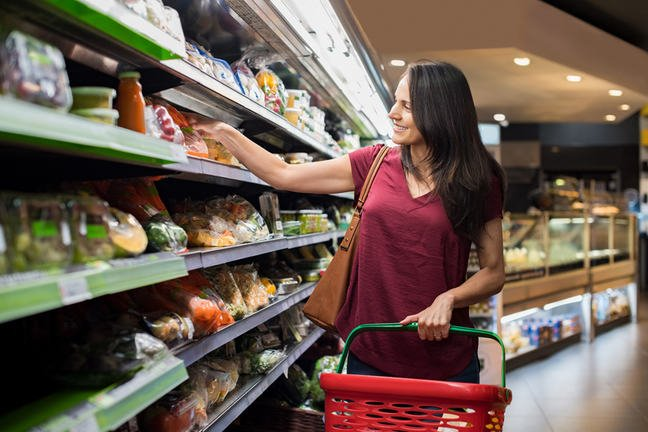 Woman shopping in fresh vegetable aisle of supermarket.
