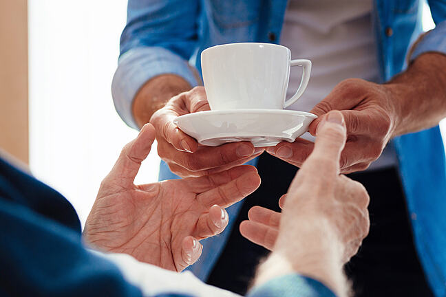 Close-up of a cup of tea being given to an elderly man