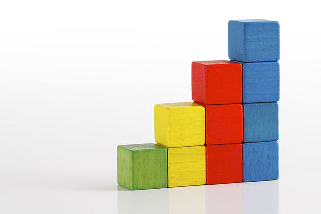 Photograph of green, yellow, red and blue wooden blocks, methodically stacked.