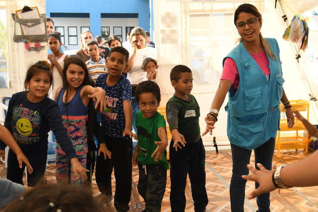 A woman wearing a blue vest is standing in a circle with young children all around her. They are playing a game where they put there right hand into the circle.