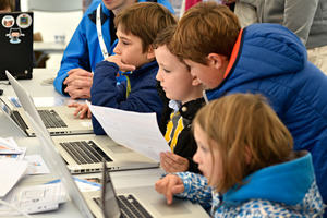 Group of young people on laptops learning how to code