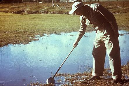 A man wearing beige overalls and a cap stands at the side of a small body of water. He is skimming the water with a larval dipper which is a bowl attached to a stick, to collect larvae.