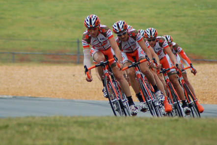 A cycling team rounds a curve in the road