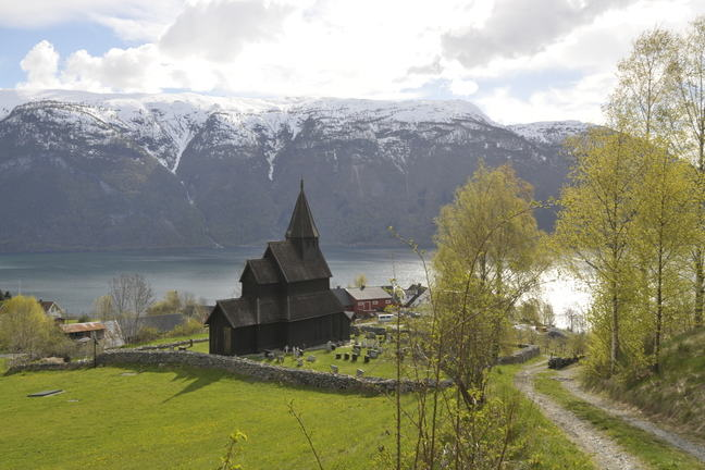 Urnes Stave Church with fjord and mountains.