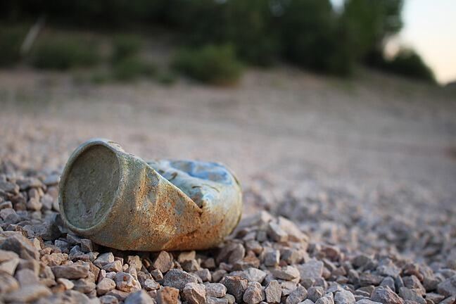 An empty finished can lying on a stoned road