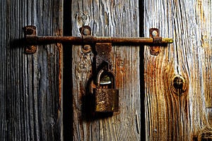 A rusted padlock on rotting timber