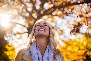 Se observa una mujer mirando al cielo y sonriendo. De fondo hay árboles y se ve el reflejo del sol.