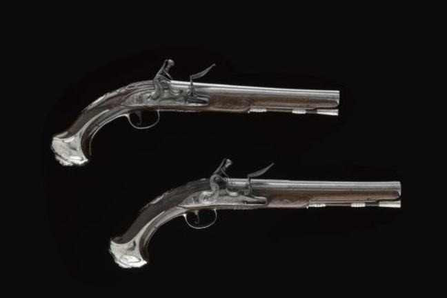 A pair of 'Queen Anne holster' pistols with silver mounts and flintlock visible, engraved with 'AMD Clanranald 1712' and 'To AMD Dalelea 1715'